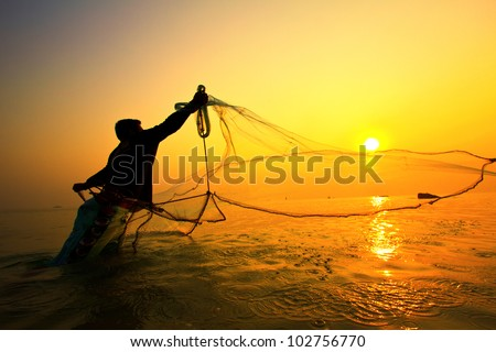 throwing fishing net during sunrise - stock photo