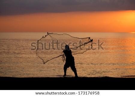 throwing fishing net during sunrise - stock photo