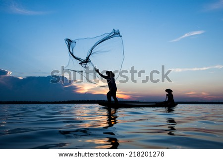 throwing fishing net during sunset on boat , thai - stock photo