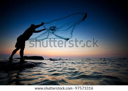 throwing fishing net during sunset , thai - stock photo