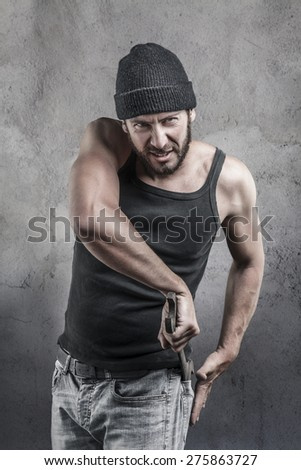 Thug preparing to use a wrench as a weapon pulling it out of the pocket of his jeans as he watches the camera with a dangerous angry expression, over a textured grey background