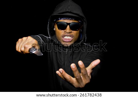 thug wearing a hoodie and holding a knife coming out of the shadows - stock photo