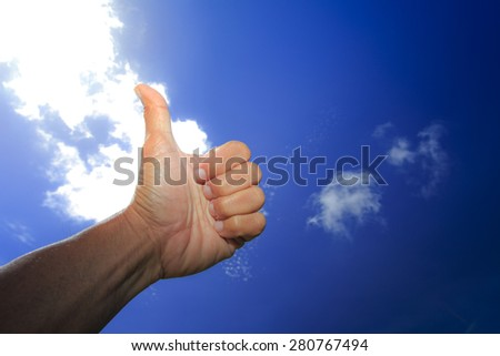 Thumb point to the deep blue sky, success and relaxing symbol. - stock photo