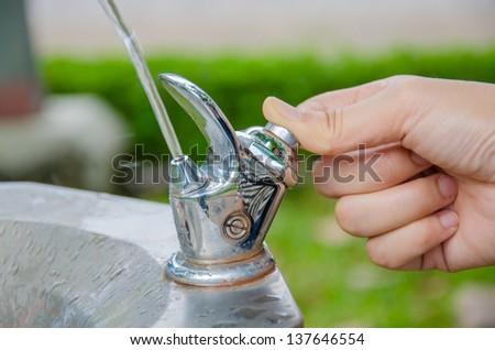 Thumb press the drinking water fountain - stock photo