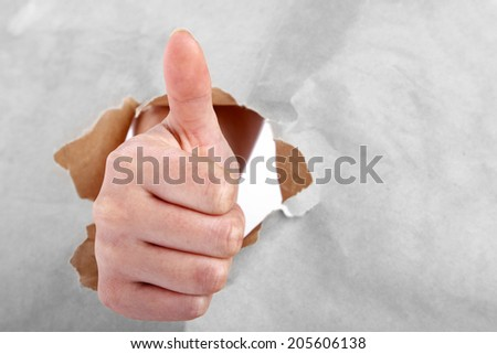 Thumb sign through ripped paper - stock photo