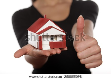 Thumb up and miniature model house in woman hand - stock photo
