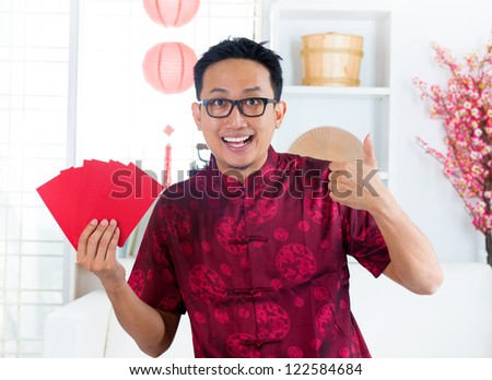 Thumb up Asian Chinese man showing many red packets / ang pow  indoors