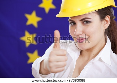 thumb up for european economy - happy woman in safety helmet over european flag - stock photo