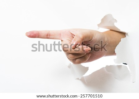 Thumb up hand gesture break through the paper wall - stock photo