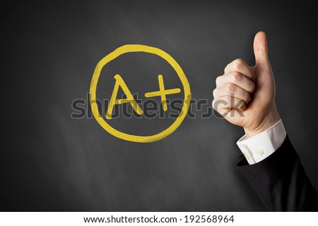 thumb up in front of chalk board with a+ grade - stock photo