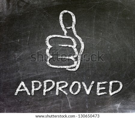 Thumb up sign drawn with chalk on a blackboard. Text written in chalk approved