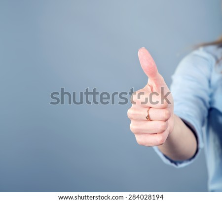 Thumb up. Women's hand shows the sign that everything is fine, everything is very good. Woman thumb up on blue background. Space for text. Left, right. Concept about the good things and the good news. - stock photo