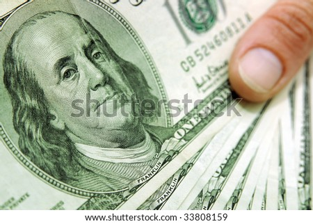 Thumb with a bundle of one hundred dollar bills - stock photo