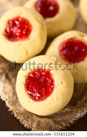 Thumbprint Christmas cookies filled with strawberry jam, photographed with natural light (Selective Focus, Focus diagonally through the middle of the first cookie)