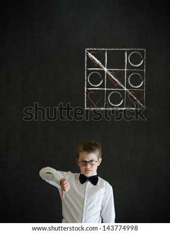 Thumbs down boy dressed up as business man with chalk tic tac toe love valentine concept on blackboard background - stock photo