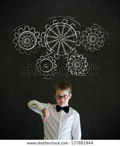 Thumbs down boy dressed up as business man with chalk turning gear cogs or gears on blackboard background - stock photo