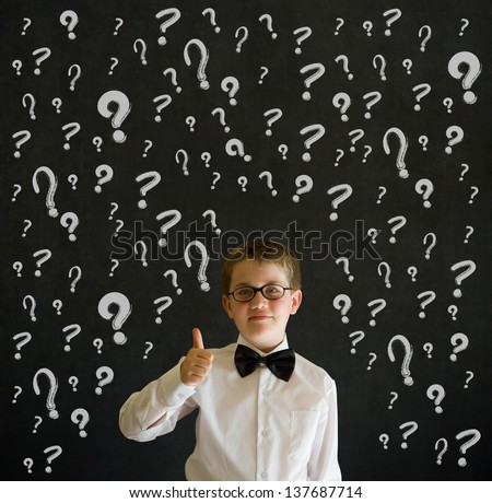 Thumbs up boy dressed up as business man with chalk questions marks on blackboard background - stock photo