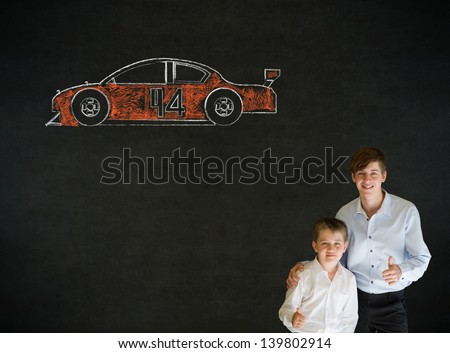 Thumbs up boy dressed up as business man with teacher man and American racing fan car on blackboard background - stock photo
