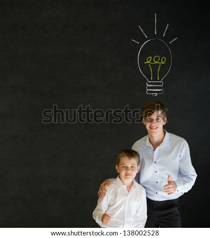 Thumbs up boy dressed up as business man with teacher man and bright idea chalk background lightbulb on blackboard background - stock photo
