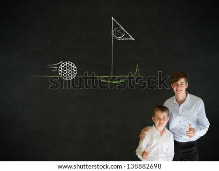 Thumbs up boy dressed up as business man with teacher man and chalk golf ball flag green on blackboard background - stock photo