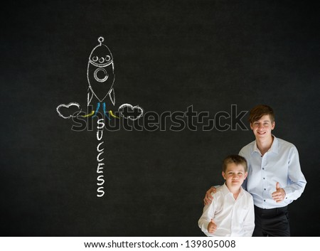Thumbs up boy dressed up as business man with teacher man and chalk success rocket on blackboard background - stock photo