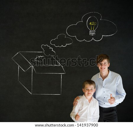 Thumbs up boy dressed up as business man with teacher man and chalk thinking out the box concept  on blackboard background - stock photo