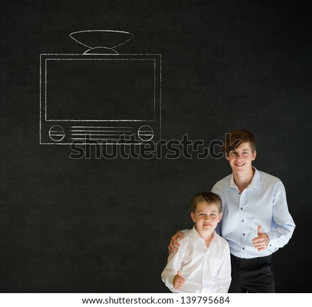 Thumbs up boy dressed up as business man with teacher man and chalk tv television on blackboard background - stock photo