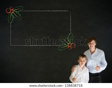 Thumbs up boy dressed up as business man with teacher man and Christmas holly to do checklist on blackboard background - stock photo