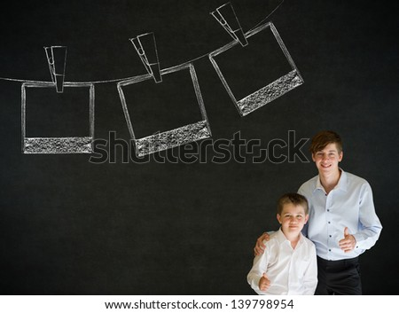 Thumbs up boy dressed up as business man with teacher man and hanging instant photograph on blackboard background - stock photo