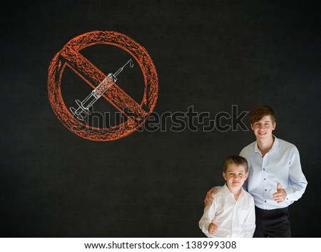 Thumbs up boy dressed up as business man with teacher man and no drugs needle sign on blackboard background - stock photo