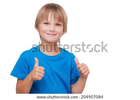 Thumbs up! Cheerful little boy showing his thumbs up and smiling while standing isolated on white - stock photo