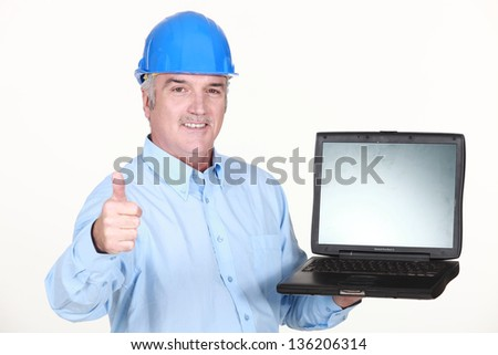 Thumbs up from an engineer with a laptop - stock photo