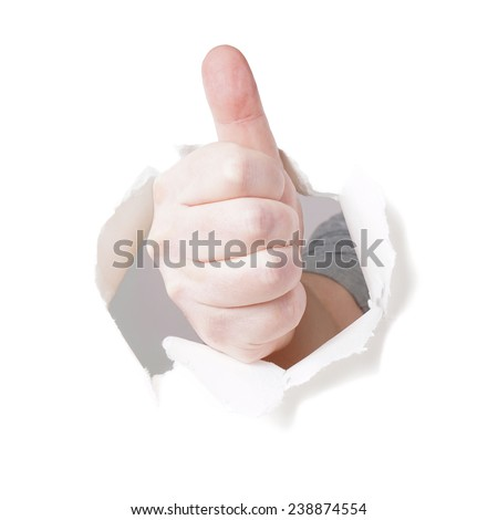 thumbs up gesture through hole in paper wall background - stock photo