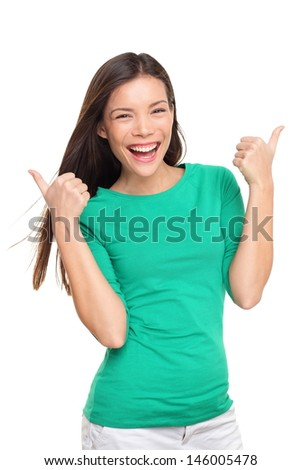Thumbs up happy excited woman isolated on white background in green t-shirt. Cheerful joyful and elated girl looking at camera. Multiracial Asian Caucasian girl in her twenties. - stock photo