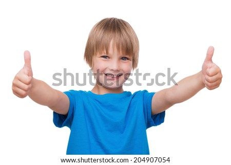 Thumbs up! Happy little boy showing his thumbs up and smiling while standing isolated on white - stock photo