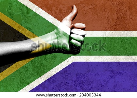 thumbs up in a South African flag placed on a textured background - stock photo