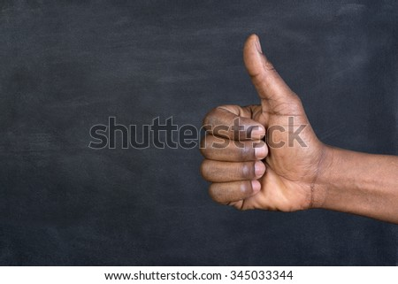 Thumbs up in front of a blackboard with copy space - stock photo