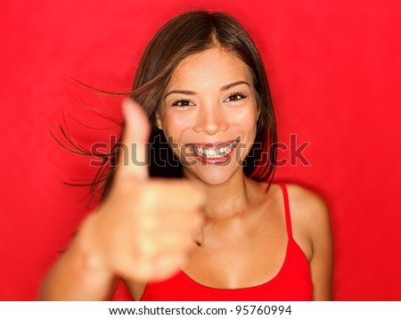 Thumbs up like woman smiling happy with natural beautiful smile on red background. Cheerful and joyful multiracial Asian / Caucasian girl looking energetic at camera showing positive hand sign. - stock photo