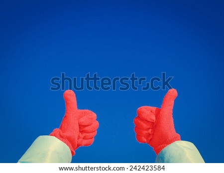 thumbs up on winter sky background - stock photo