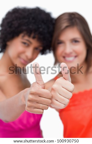 Thumbs up showed by two smiling teenage friends - stock photo