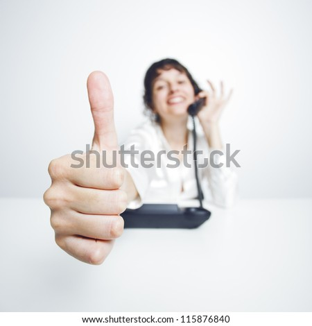 thumbs up shown by a happy, smiling young woman working at her office desk while phoning