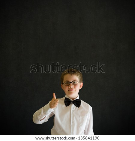 Thumbs up sign boy dressed up as business man, teacher or student on blackboard background - stock photo