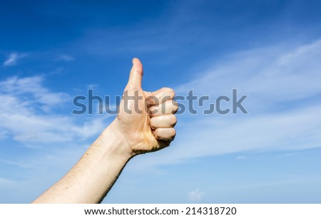 thumbs up sign under blue sky - stock photo