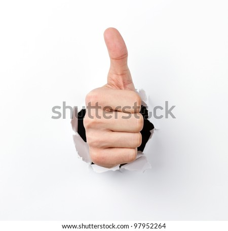 Thumbs up through the hole in paper sheet - stock photo