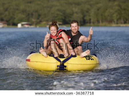 Thumbs up while tubing on a lake