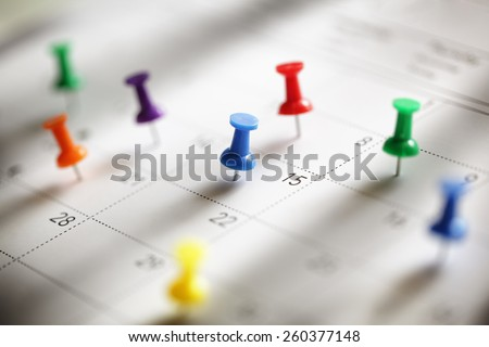 Thumbtack in calendar concept for busy, appointment and meeting reminder - stock photo