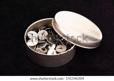 thumbtacks in a round metal box, photo on a dark blue background.