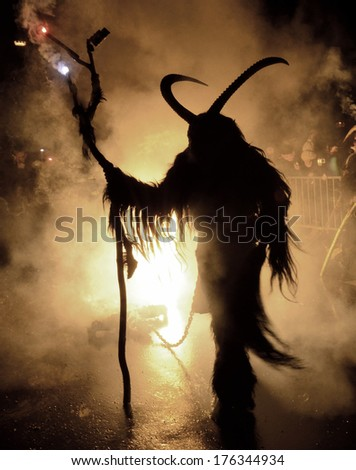 THUMERSBACH, AUSTRIA - CIRCA DECEMBER 2013: Unidentified man wears Krampus (devil) mask at traditional procession on December, 2013 in Thumersbach. - stock photo