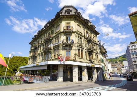 THUN, SWITZERLAND - SEPTEMBER 08, 2015: The massive building with a decorated facade. The ground floor La Perla restaurant located in the city, its terrace situated on the banks of the Aare River - stock photo
