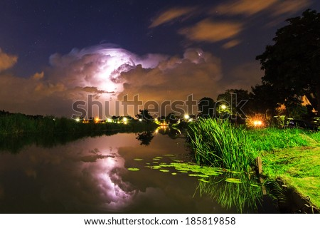 Thunderclouds and lightning reflected in the river at night in the Netherlands - stock photo